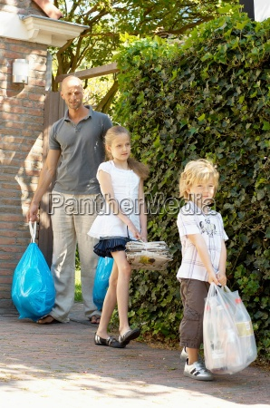 father and children carrying garbage den