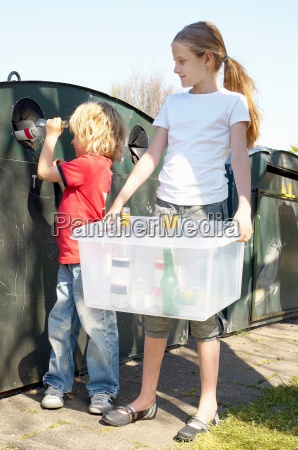 two children recycling bottles