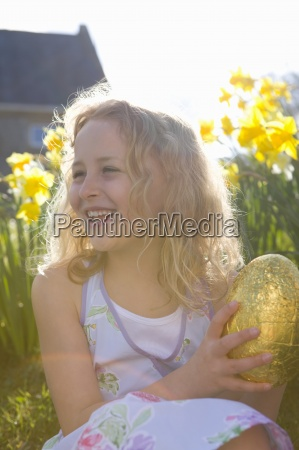 girl finding chocolate easter egg in