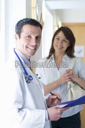 doctor reviewing medical chart with female