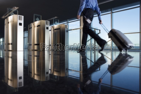 man with luggage walking towards security