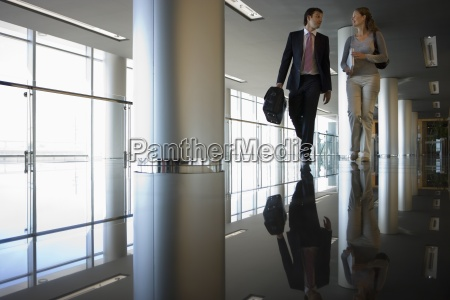 businesswoman and businessman walking in large