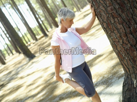 active senior woman leaning against tree