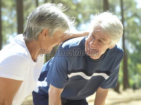 senior couple in sportswear taking break