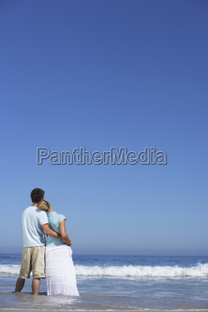 couple standing on beach looking at