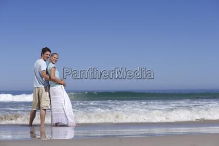 couple standing on beach beside sea