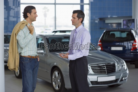 car salesman talking to male customer