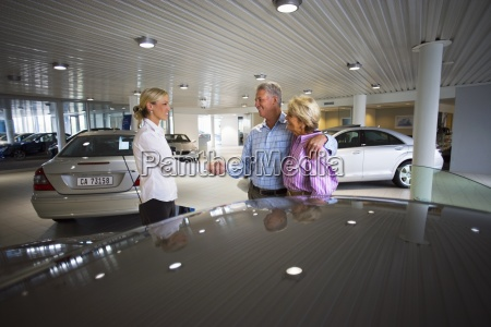 car saleswoman and senior couple standing