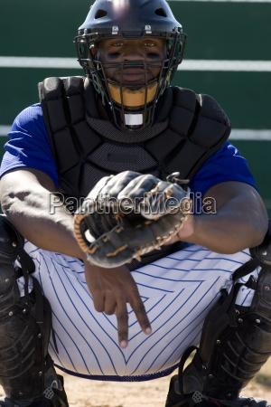 baseball catcher crouching on pitch making