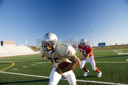 american football player chasing opposing player