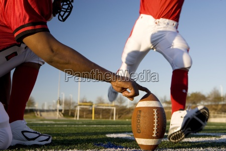 american football player attempting to kick