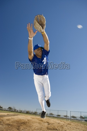 baseball player in blue uniform diving