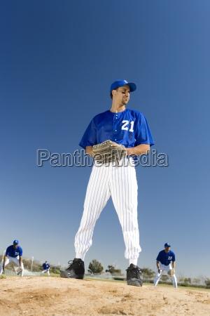 baseball pitcher in blue uniform preparing