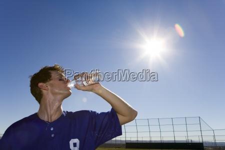 sportsman drinking water from bottle on