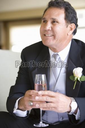 senior groom in formalwear sitting on