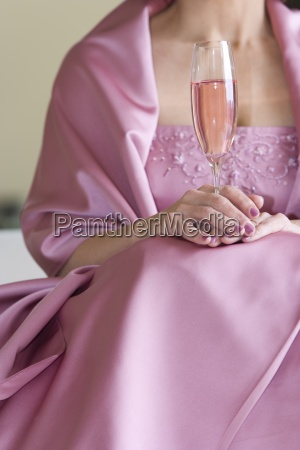 senior woman in pink dress holding