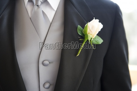 groom wearing buttonhole close up mid