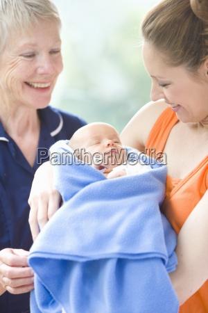 proud grandmother watches daughter holding newborn