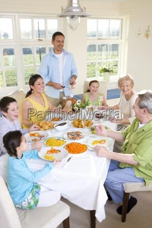 multi generation family eating dinner at