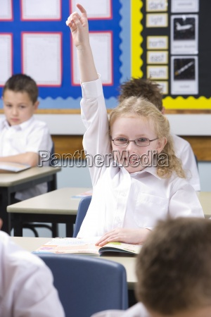 school girl wearing eyeglasses raising hand