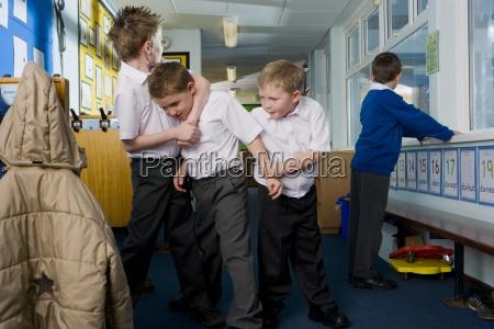 aggressive school boys rough housing in