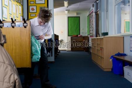 school boy taking something from bag