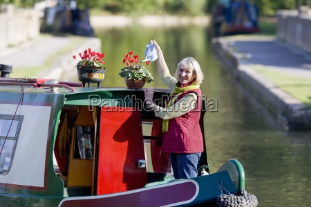 woman watering potted flowers on boat
