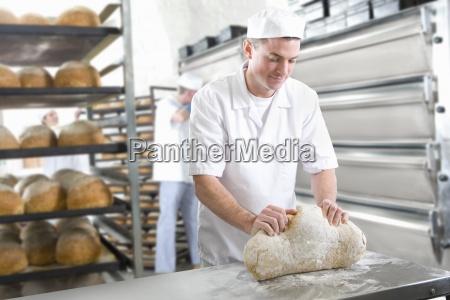 baker kneading bread dough in bakery