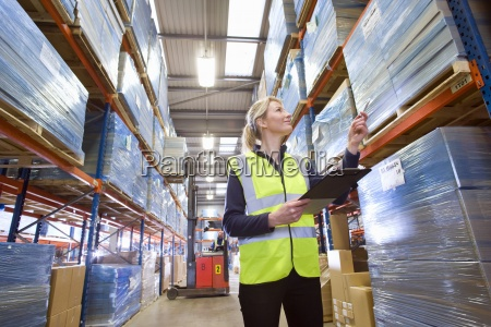 warehouse worker holding clipboard and checking