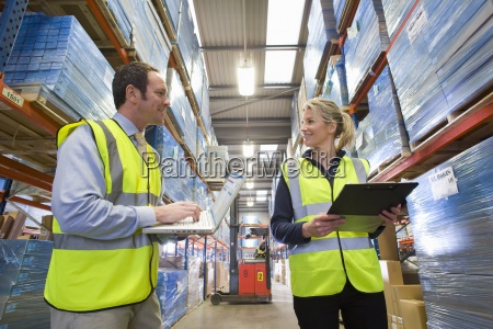 warehouse manager and worker checking inventory