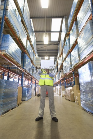 warehouse manager holding laptop in aisle