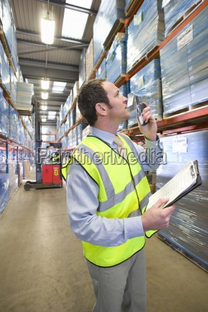 warehouse manager holding clipboard and using
