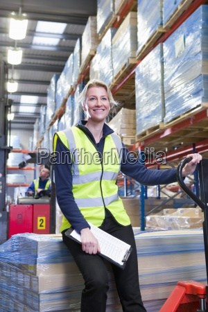 smiling female warehouse manager holding clipboard
