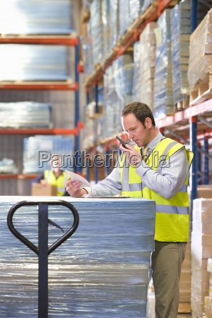 warehouse manager using walkie talkie and