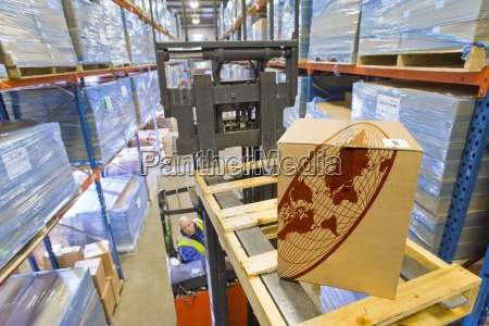 warehouse worker moving cardboard box on