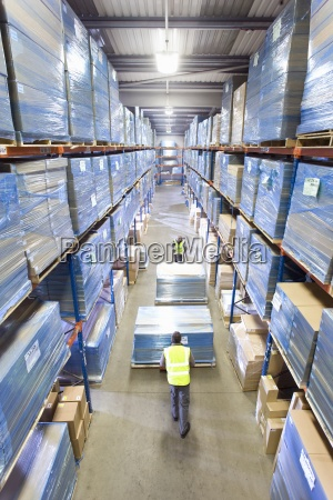 warehouse workers pushing pallet trucks with
