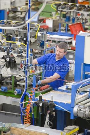 lavoratore che lavora macchinari sulla linea