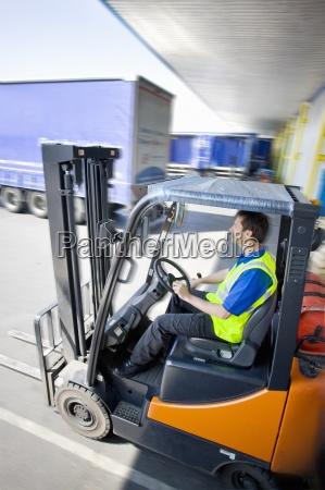 worker driving forklift on loading dock