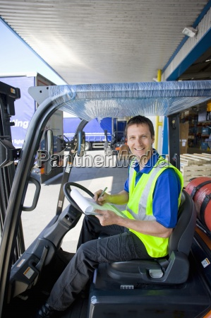 worker in forklift writing on clipboard