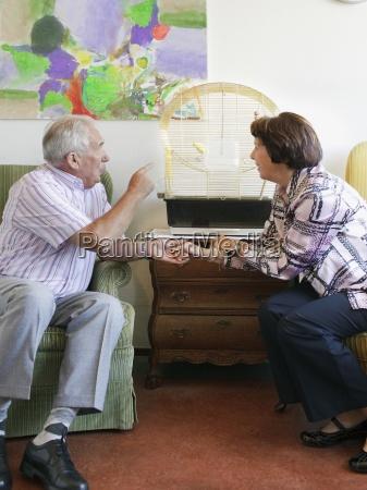a senior couple discussing a bird