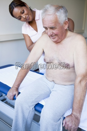 a massage therapist treating a senior