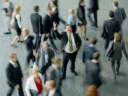 a businessman in a crowd making