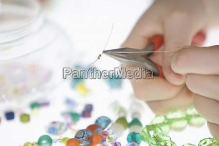 a young girl making a bead