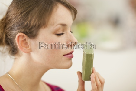 a young woman smelling a bar