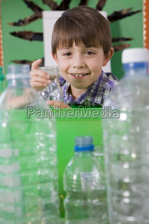 smiling student putting glass into recycling