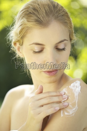 portrait of young woman putting lotion