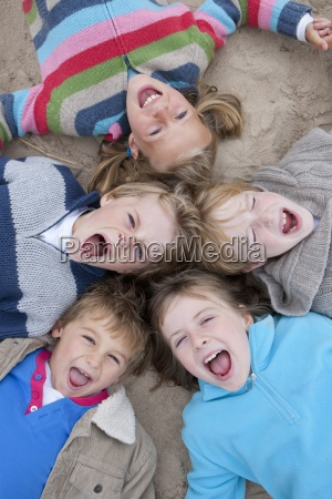overhead shot of excited children lying