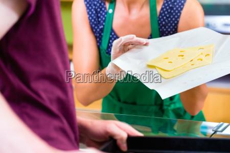 saleswoman at kaesetheke offers cheese