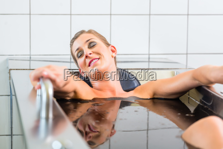 young woman in mud bath at