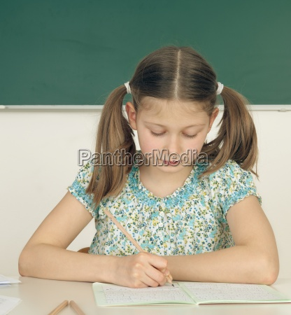 schoolgirl is sitting at the table